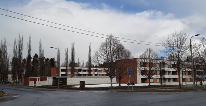 Risteys, jonka toisella puolella on matalia kerrostaloja. Talojen julkisivu on valkoinen, ja muilta osilta punatiiltä